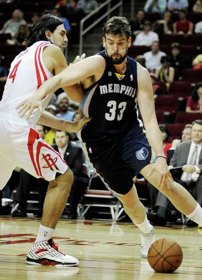 Memphis Grizzlies' Marc Gasol (33) drives the ball around Houston Rockets' Luis Scola (4) in the first half of an NBA basketball game, Friday, March 30, 2012, in Houston. (AP Photo/Pat Sullivan) Photo: Pat Sullivan, Associated Press / AP