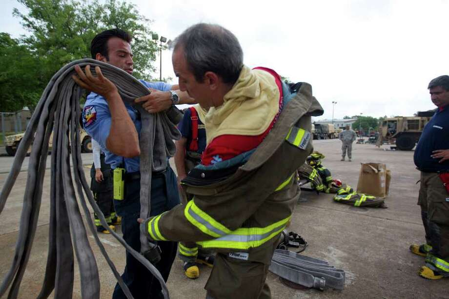 Argentinian firefighter Javier Astorja gets instruction from HFD Cpt. Ruy Lozano, left, during a high rise training drill at the HFD Val Jahnke Training Facility Friday, March 30, 2012, in Houston. For the fourth year in a row, 18, firefighters representing Columbia, Venezuela, Mexico, the Dominican Republic, Ecuador and Argentina received high-rise firefighting, incident command familiarization and house advancement technique training. Photo: Johnny Hanson, Houston Chronicle / © 2012  Houston Chronicle