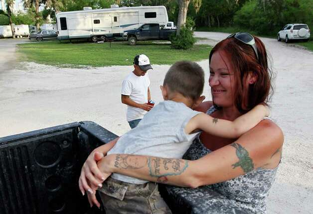 METRO -- Nicole Garcia hugs her son, Johnny Joe Garcia, III, 3, at the Tips Park in Three Rivers, Texas, Monday, March 26, 2012. In back is her husband, Johnny Joe Garcia, Jr. The family has lived at the park for the past two months. He is a pipeline trucker.  Jerry Lara/San Antonio Express-News Photo: JERRY LARA, San Antonio Express-News / SAN ANTONIO EXPRESS-NEWS