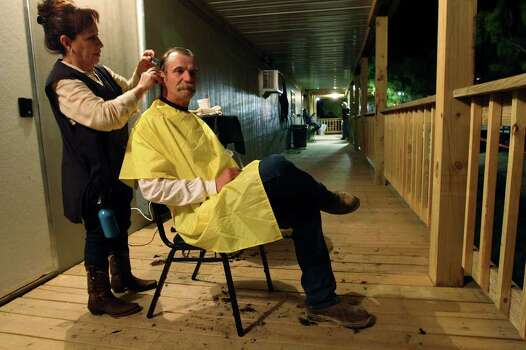 "METRO -- Alan Roberts, 53, gets a haircut from Josie Wimberley at a man camp in Carrizo Springs, Texas, Wednesday, March 21, 2012. An oilfield worker all his adult life, Roberts said, ""The good old days were the hard old days. If you lived on a drilling rig, you lived in a little room with six or eight guys on top of you."" Jerry Lara/San Antonio Express-News Photo: Jerry Lara, San Antonio Express-News / © San Antonio Express-News"