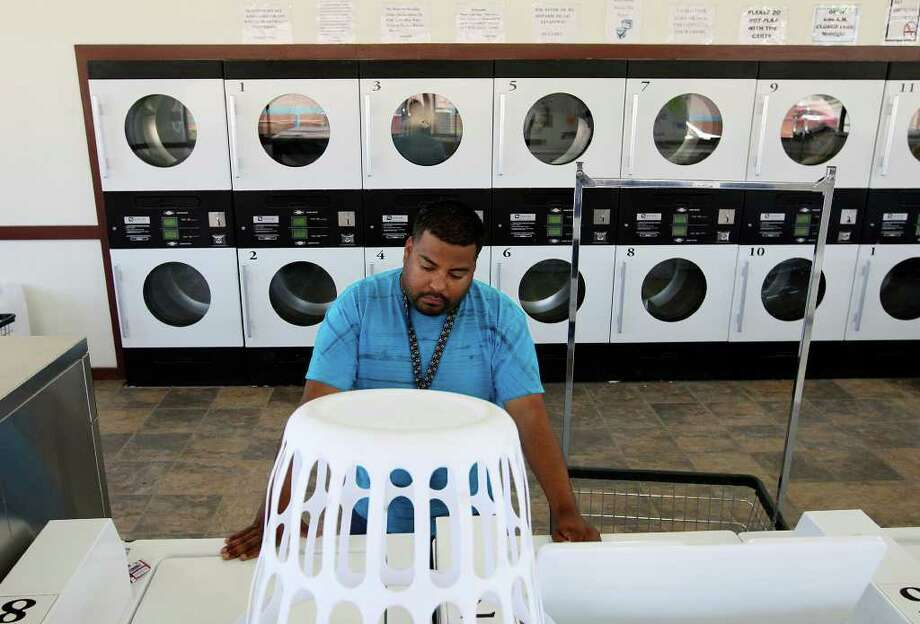 METRO -- Jorge Castillo, 24, of San Juan, Texas, gets his laundry done at a laundromat in Carrizo Springs, Texas, Wednesday, March 28, 2012. The Rio Grande Valley resident took a job on a roustabout crew. The job is one of the lowest in the oil business and entails digging trenches, washing pits and moving rigs. Together with roommate and fellow worker, Juan Garcia, they earn $13 an hour and each pay $400 a month for a FEMA trailer in Asherton, Texas.  But when there is no work, there is no money. The only jobs in the Valley available to Castillo would pay the minimum wage. Jerry Lara/San Antonio Express-News Photo: Jerry Lara, San Antonio Express-News / © San Antonio Express-News