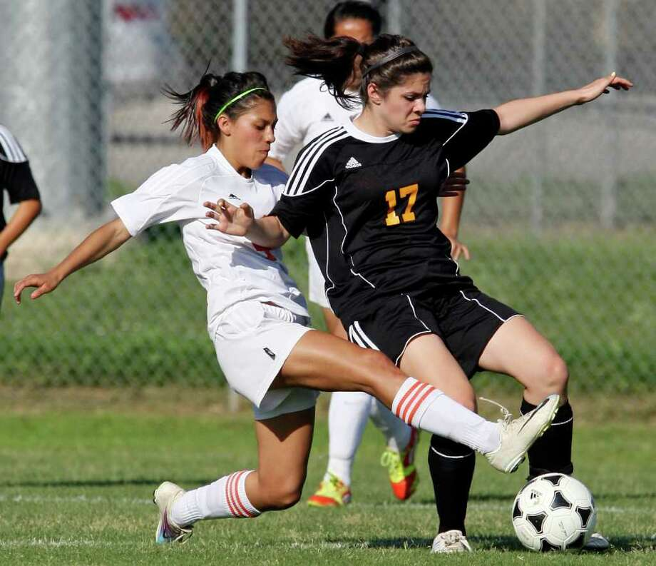 Burbank's Rose Villarreal (left) and Brennan's Elexandra Lombrado struggle for control of the ball during first half action of their Class 4A first round playoff game Friday March 30, 2012 at SAISD Sports Complex. Photo: EDWARD A. ORNELAS, Express-News / © SAN ANTONIO EXPRESS-NEWS (NFS)