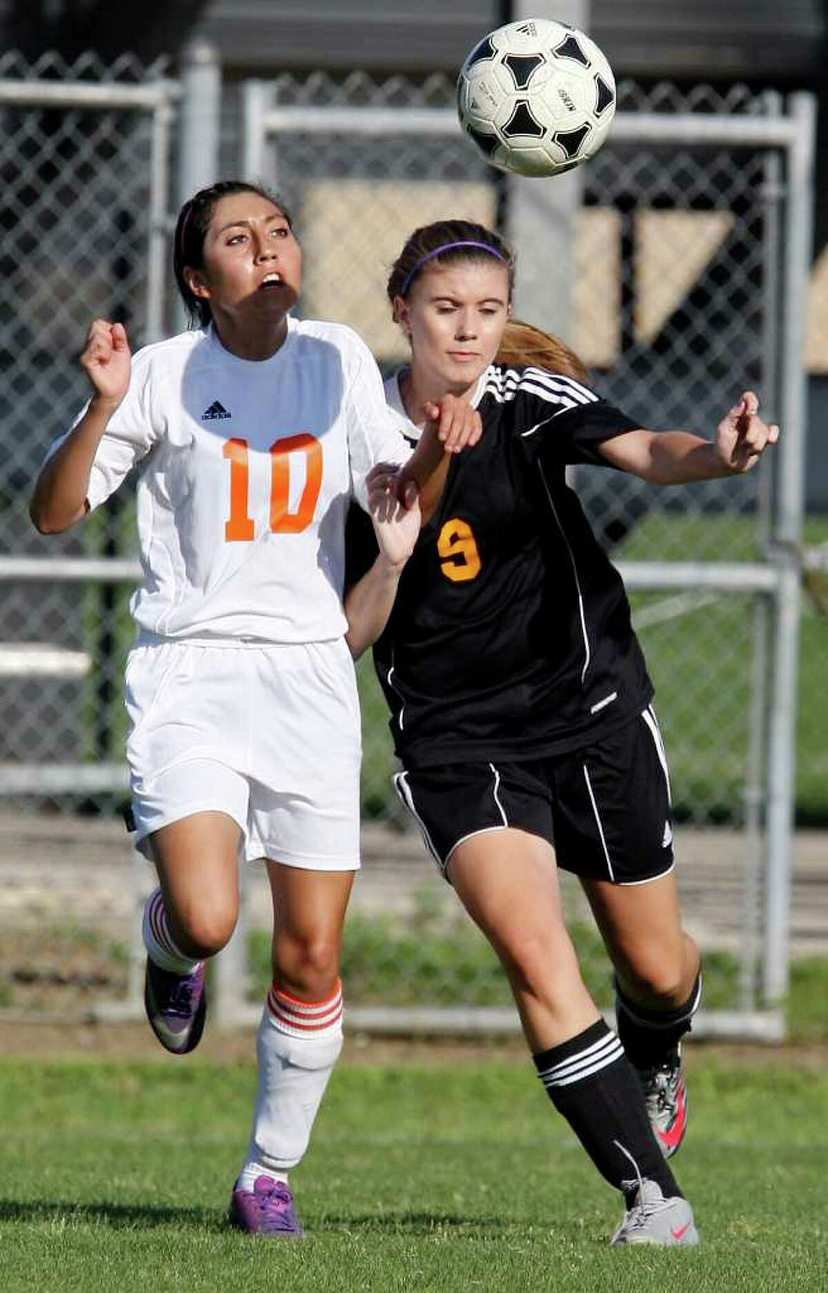 Burbank's Denise Ramirez (left) and Brennan's Caitlin Gabehart chase after the ball during first half action of their Class 4A first round playoff game Friday March 30, 2012 at SAISD Sports Complex.