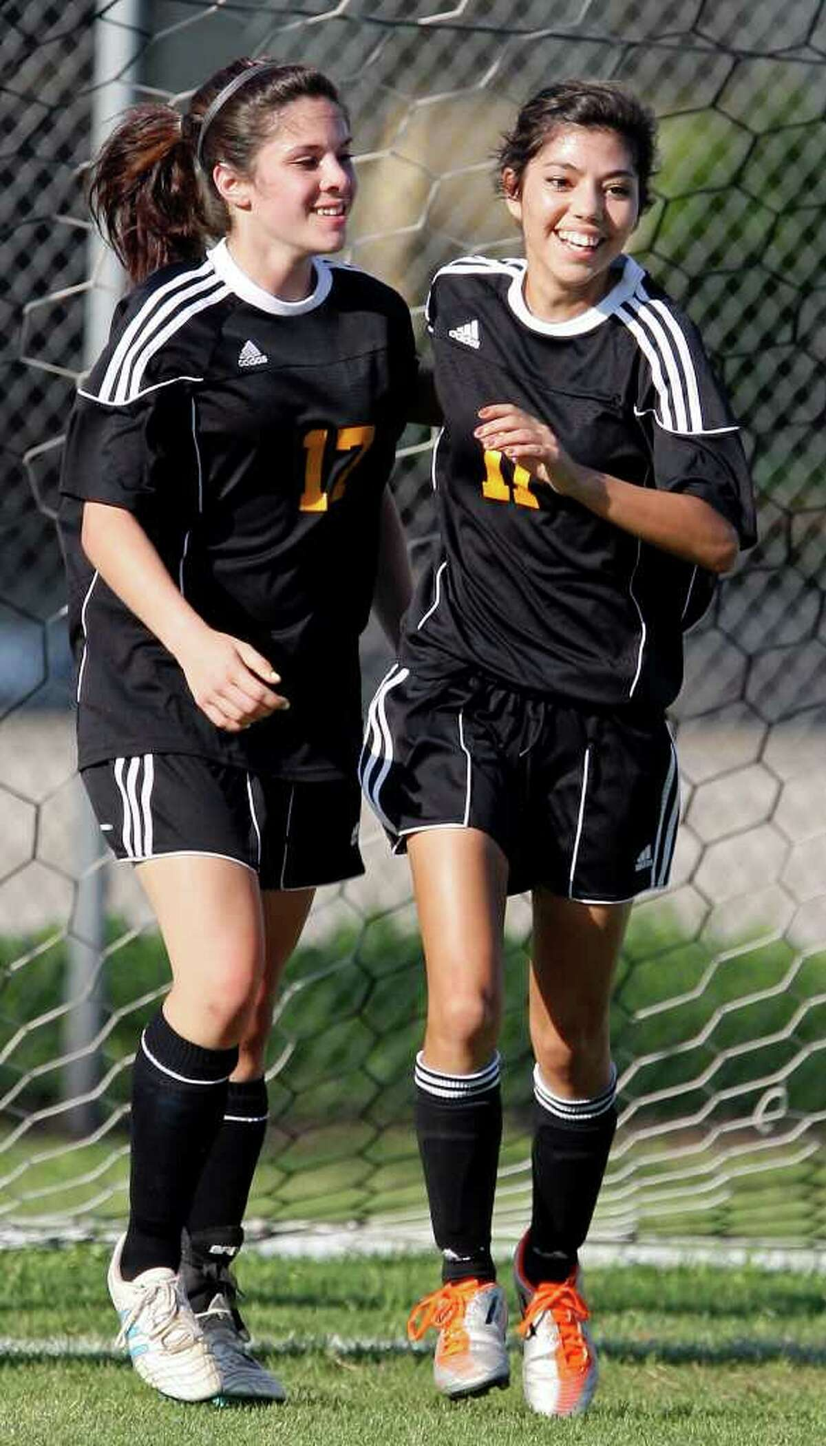 Brennan's Elexandra Lombrado (left) celebrates with teammate Brennan's Madelyn Ruiz after Ruiz scored a goal against Burbank during first half action of their Class 4A first round playoff game Friday March 30, 2012 at SAISD Sports Complex.