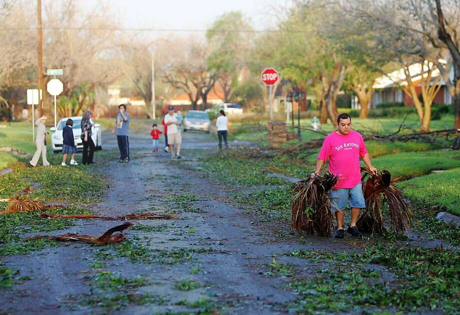 David Perez removes debris from the road Friday March 30, 2012 in McAllen, Texas. Several streets and homes were flooded in the area after heavy rains, winds and hail hit the area Thursday night.  (AP Photo/The Monitor, Gabe Hernandez)  MAGS OUT; TV OUT Photo: Gabe Hernandez, Associated Press