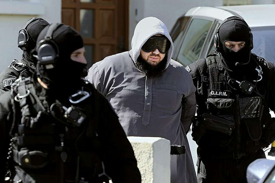 French members of the French National Police Intervention Group (GIPN) arrest Forsane Alizza Islamic radical group's leader Mohamed Achamlane after searching his house in Bouguenais, western France, on March 30, 2012 as part of down raids in several French cities. French police arrested 19 people in a crackdown on suspected Islamist networks as President Nicolas Sarkozy made the battle against extremism the keynote of his re-election campaign. Photo: Jean-sebastien Evrard, AFP/Getty Images