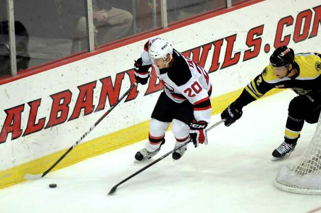 Devils' Matt Taormina (20), left, controls the puck as Providence Bruins' Andrew Bodnarchuk (2) pursues behind the net during their hockey game on Friday, March 30, 2012, at Times Union Center in Albany, N.Y. (Cindy Schultz / Times Union) Photo: Cindy Schultz / 00016873C