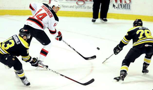 Devils' Nathan Perkovich (14), center, charges the puck against Providence Bruins' Kirk MacDonald (13), left, and Kevan Miller (28) during their hockey game on Friday, March 30, 2012, at Times Union Center in Albany, N.Y. (Cindy Schultz / Times Union) Photo: Cindy Schultz / 00016873C