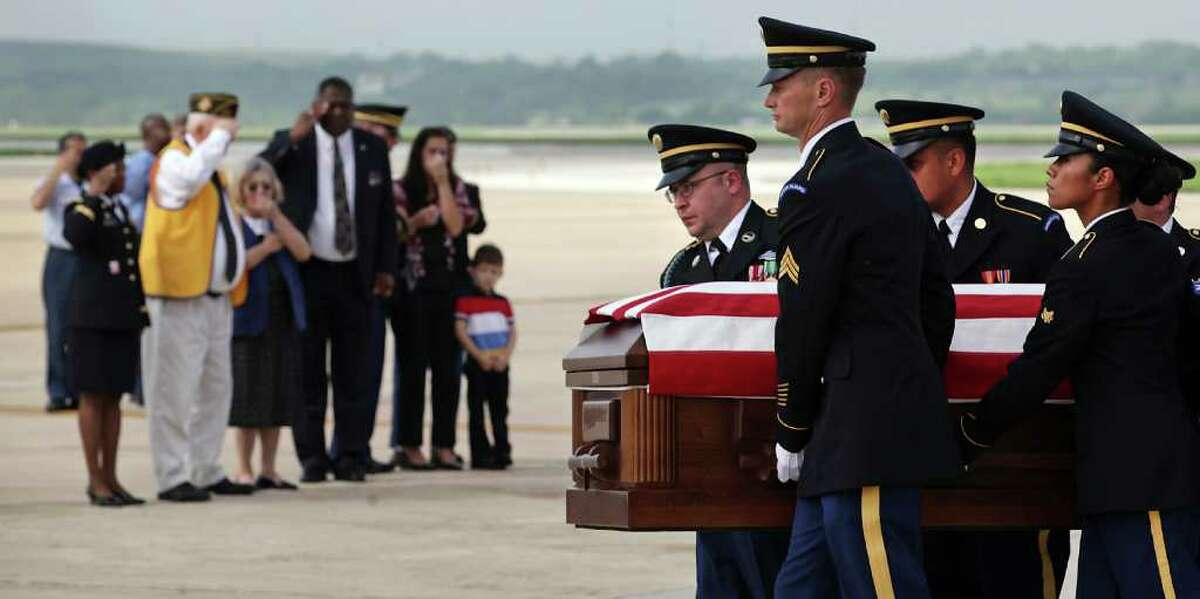 Members of the U.S. Army Honor Guard carry the remains of Army 1st Lt. Clovis T. Ray as family members, including parents Bob and Cecilia Ray, wife Shannon Ray and son Dean Ray, 5, stand nearby after Ray arrived at the Kelly Field Flightline. Ray died March 15th in the Kunar province in Afghanistan.