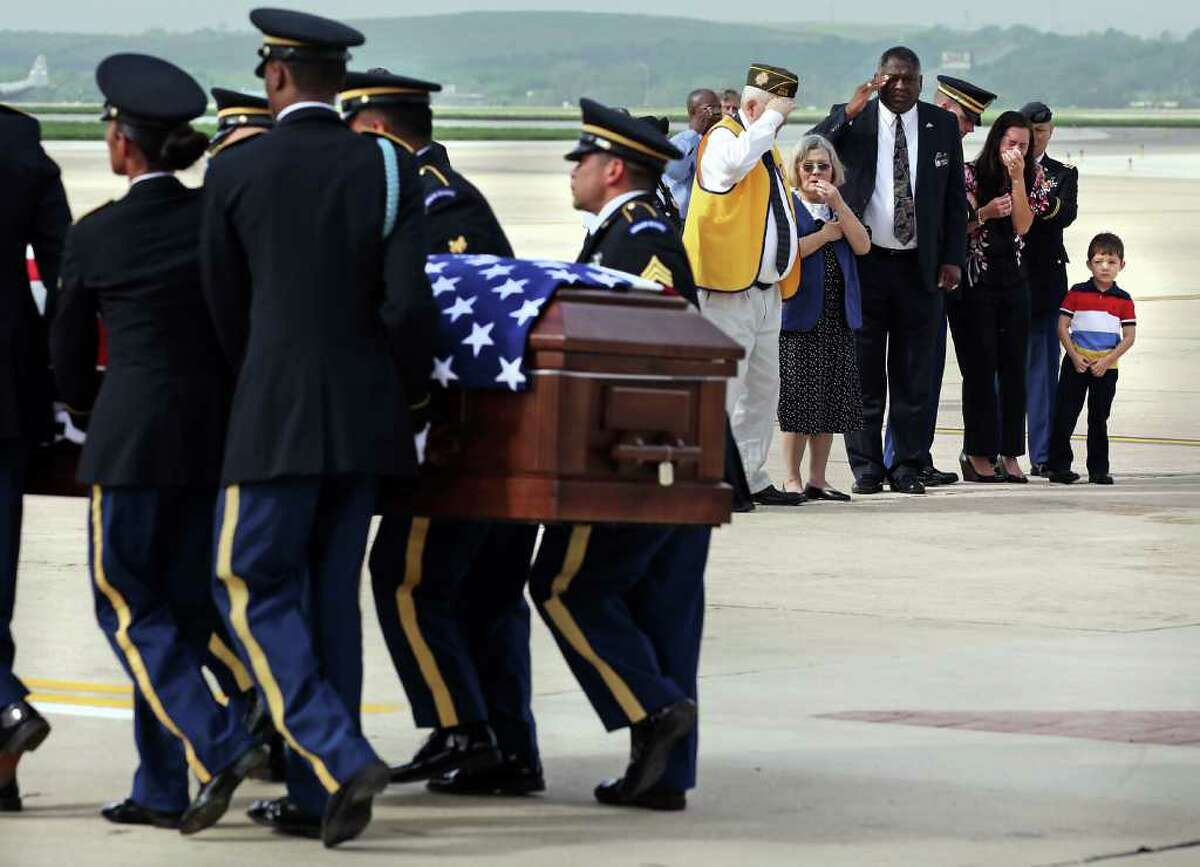 Dean Ray, 5, right, standing next to his mother Shannon Ray, watches as U.S. Army Honor Guard carry the remains of his father Army 1st Lt. Clovis T. Ray after arriving at the Kelly Field Flightline. Rays father, Bob Ray, in yellow vest, salutes, standing by his wife Cecilia Kim Ray. Ray died March 15th in the Kunar province in Afghanistan.