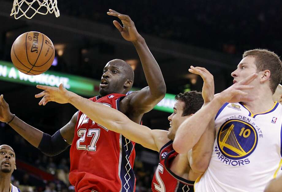 New Jersey Nets' Johan Petro (27) and Kris Humphries, center, go after a rebound as Golden State Warriors' David Lee (10) defends during the first half of an NBA basketball game, Friday, March 30, 2012, in Oakland, Calif. Photo: Ben Margot, Associated Press