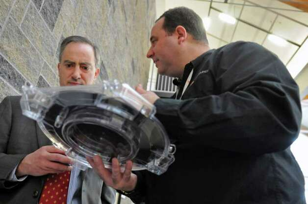 GlobalFoundries Sean Calvelli, right, holds a single wafer carrier while talking with Village of Ballston Spa attorney Jim Fauci, left, about the chip making process during a gathering of local officials at the HVCC TEC-SMART campus on Wednesday March 28, 2012 in Malta, NY. (Philip Kamrass / Times Union ) Photo: Philip Kamrass / 00016997A