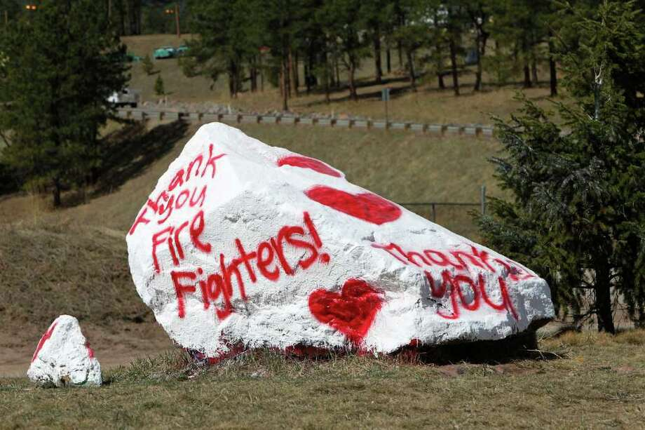 """A large boulder with  """"Thank You Firefighters!"""" sits at the entrance to Conifer High School where firefighters have setup their command center in Conifer, Colo., on Saturday, March 31, 2012.  As many as 500 firefighters are battling the the Lower North Fork Wildfire near Conifer that killed two people after it started Monday afternoon. Access to the burn area was restricted Saturday because of expected high winds. Photo: AP"""