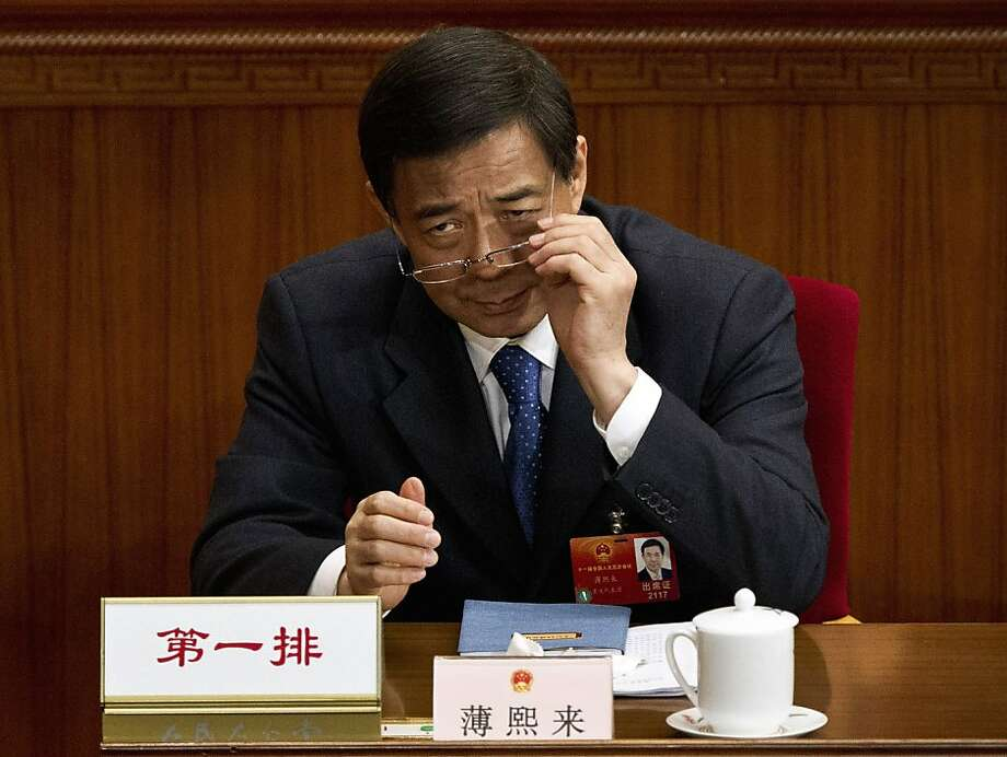 FILE - In this March 11, 2012 photo, Chongqing party secretary Bo Xilai puts on his glasses during a plenary session of the National People's Congress at the Great Hall of the People in Beijing.  Bo Xilai, one of China's highest-profile politicians interfered in an investigation involving a family member before he was fired last week, according to a leaked transcript that has escalated what already was the country's biggest political scandal in years. (AP Photo/Andy Wong) Photo: Andy Wong, Associated Press