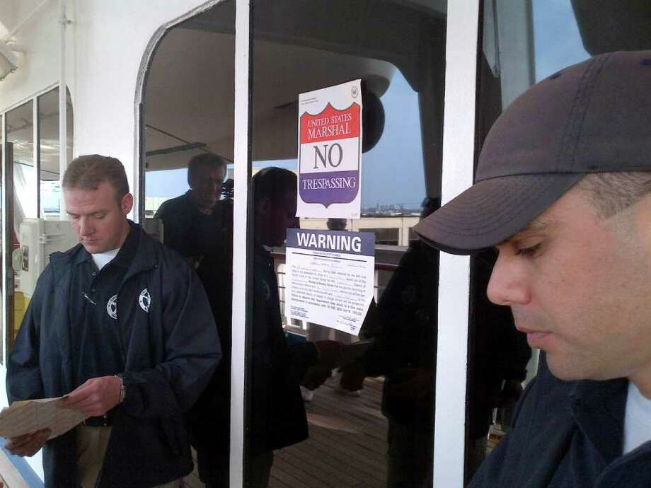 In this picture provided by the Eaves Law Firm on Saturday, March 31, 2012, unidentified US Marshals are seen enforcing an arrest warrant on board of the Carnival Triumph cruise ship moored at Galveston harbor, TX, U.S.A., Saturday, March 31, 2012. An arrest warrant was issued on Friday for the MS Carnival Triumph, a 2,758-passenger cruise liner based in Galveston, that is owned by the same company that owns the Costa Concordia, the luxury cruise ship that ran aground off the coast of central Italy in January killing some 30 people. U.S. Magistrate Judge John Froeschner of Galveston ordered the ship held in a $10 million lawsuit filed by the family of a German tourist who died aboard the Costa Concordia shipwreck off the Italian coast. Photo: AP / Eaves Law Firm