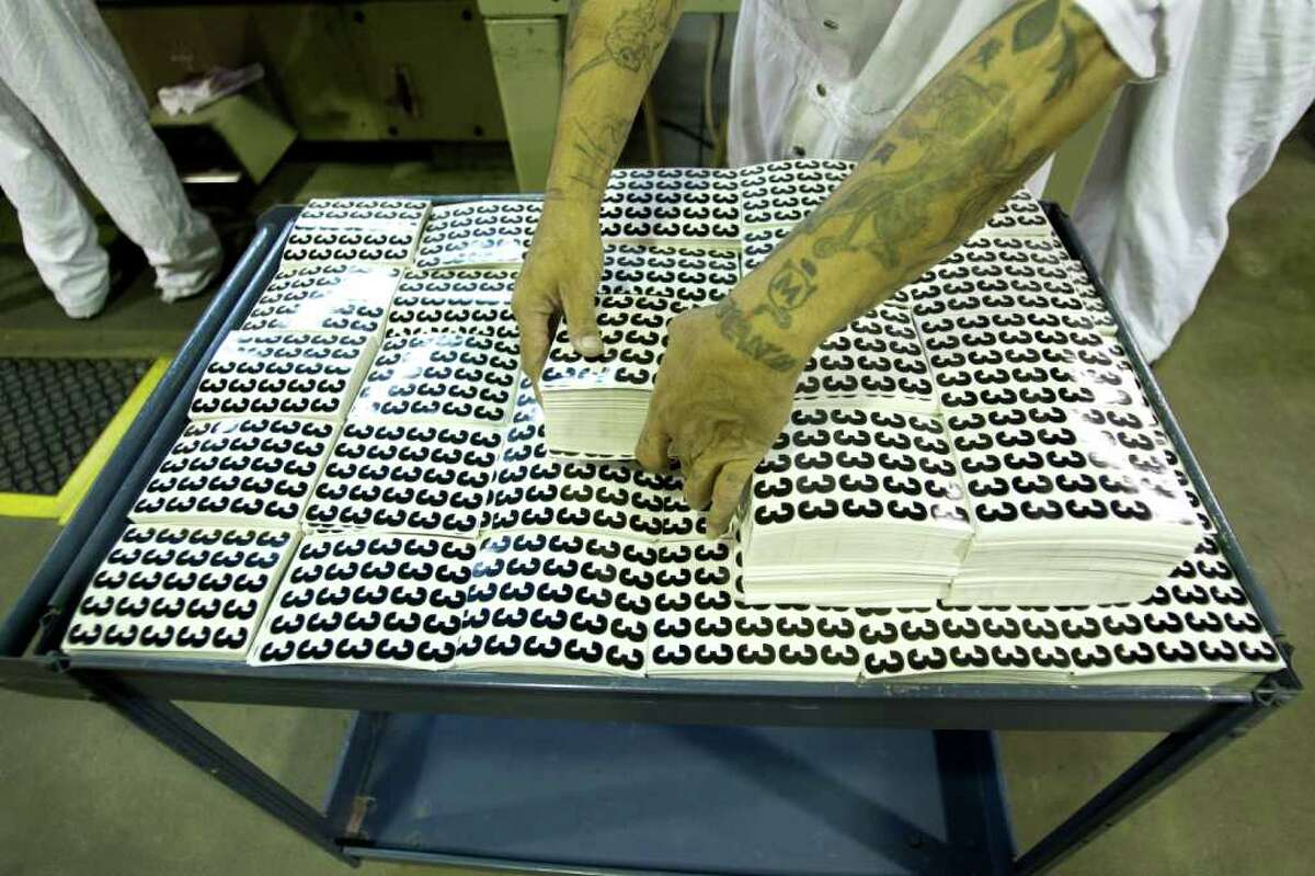 An inmate sorts adhesive numbers in the graphics plant at the Wynne Unit. Other items produced by Texas Correctional Industries include signs, banners, departmental awards, furniture, shoes and license plates.
