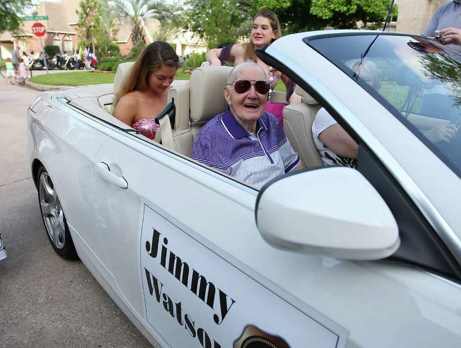 "Jimmy Watson smiles from his convertible as ""pretty girls"" Aurelie Hernandez, 17, left, and Samantha Stack, 20, sit in the back seat during Watson's parade through the Wimbledon Champions subdivision, Saturday, March 31, 2012, in Spring. Watson, 88, a WWII veteran, who served in Patton's army was honored by his neighbors for his hard work with FEMA to help the subdivision get out from a 100-year flood plain to a 500-year flood plain among other things. He requested that he be surrounded by ""pretty girls"" during the parade. Photo: Karen Warren, Houston Chronicle / © 2012  Houston Chronicle"