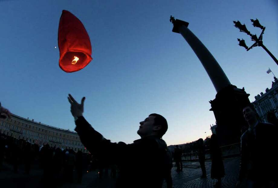A man launches a paper lantern during a ceremony to mark Earth Hour at Palace Square in St.Petersburg, Russia, Saturday, March 31, 2012. Earth Hour takes place worldwide at 8.30 p.m. local times and is a global call to turn off lights for 60 minutes in a bid to highlight the global climate change. Photo: Dmitry Lovetsky, Associated Press / AP
