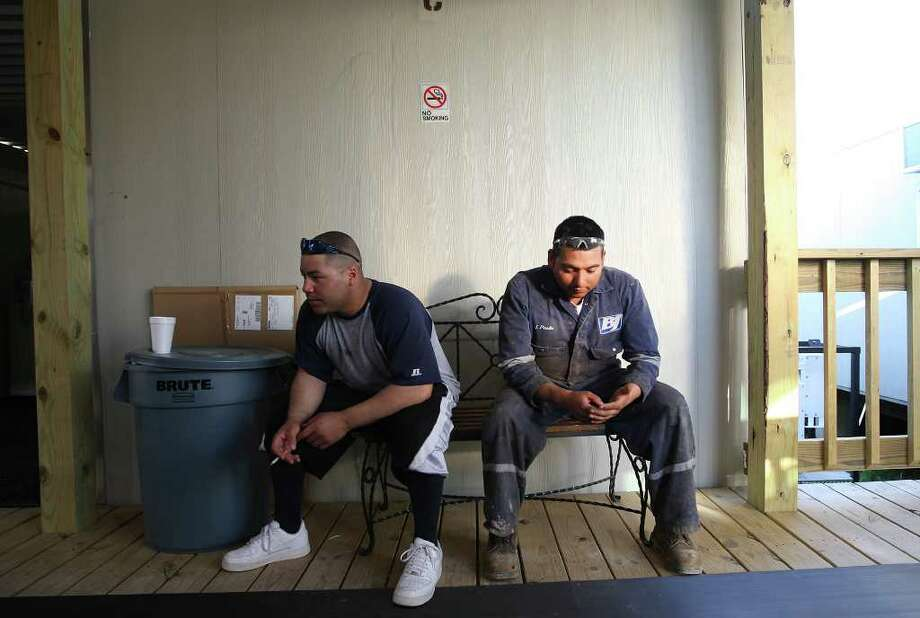 METRO -- Jose Tapia, 28, left, and Jose Pineda, 27, of Laredo, wait for their accommodations at the Mesquite Lodge in Carrizo Springs, Texas, Monday, March 19, 2012. Hotels, motels, man camps and RV parks are springing up throughout the Eagle Ford Shale counties. The workforce is now around 20,000.  Jerry Lara/San Antonio Express-News Photo: Jerry Lara, San Antonio Express-News / © San Antonio Express-News