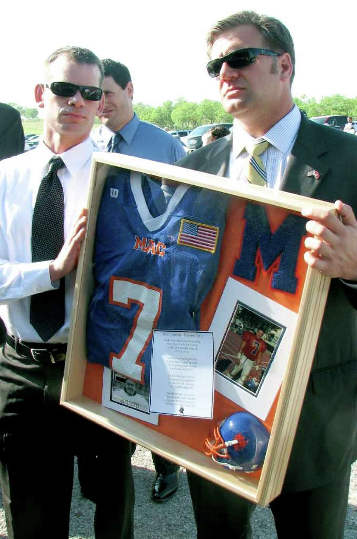 Andrew Borene, right, who played football with 1st Lt. Clovis Ray at Macalester College in St. Paul., Minn., holds a frame containing memorabilia as he waits to enter the Live Oak County Coliseum south of Three Rivers. The memorabilia includes a photo of Ray and a jersey with Ray's number on it.