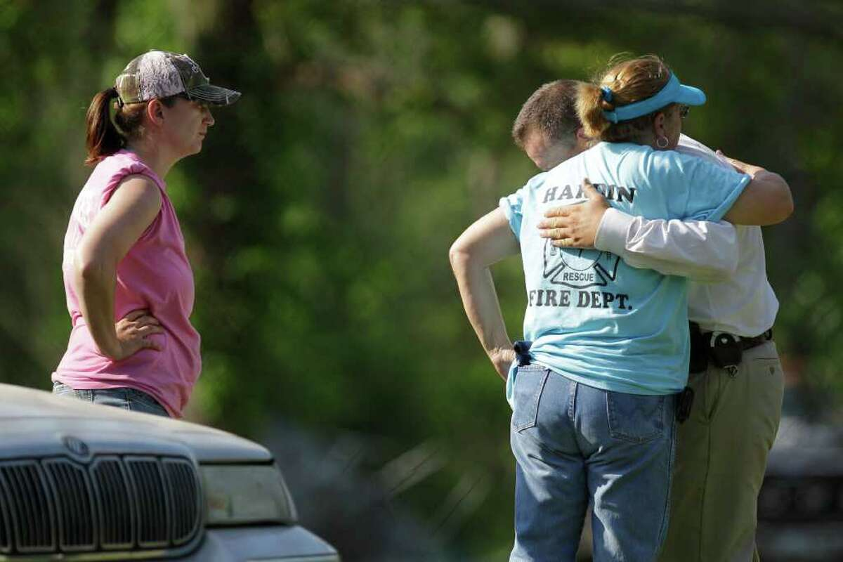 Serena Miller, left, with Cypress Lakes VFD, waits as Laura Potetz, center, with the Hardin VFD hugs Liberty County Sheriff's Captain Rex Evans after the body of 2-year-old Devon Davis was found Saturday, March 31, 2012 near the Liberty County home where he disappeared on Tuesday.