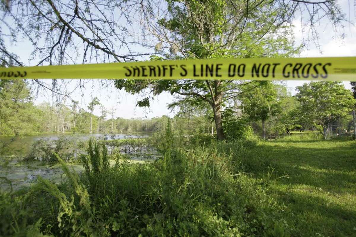 Police tape at the pond in the Sam Houston Lakes Estate subdivision where the body of 2-year-old Devon Davis was found Saturday, March 31, 2012 after disappearing on Tuesday. The boy's body was found in the algae-covered pond about 300 yards from the home. Devon and his family had only been living at the home in for six days. They recently moved from Virginia, and were staying with a family friend.