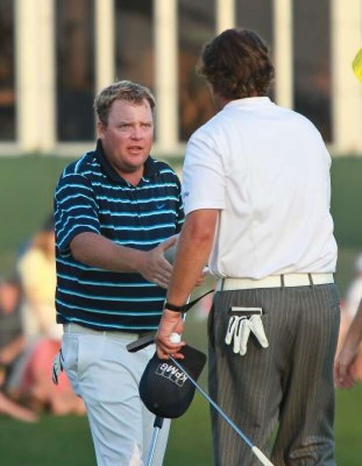 Carl Pettersson, facing, shakes hands with Phil Mickelson after they finished the third round. (Nick de la Torre / Houston Chronicle)