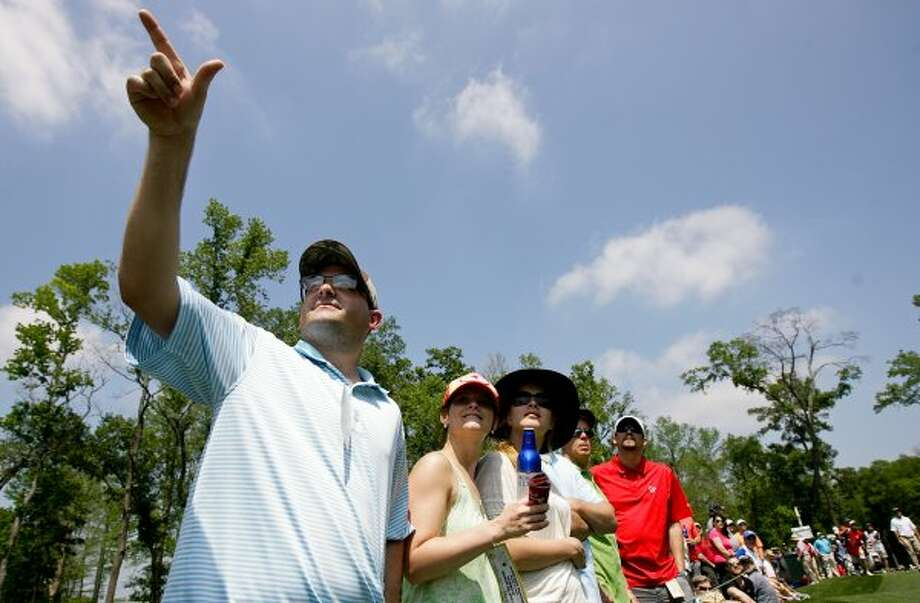 Alan Wallace points out where the ball is going to his wife Tiffany, next to Alan, and his friends as they watch golf action from the second hole during the third round. (Nick de la Torre / Houston Chronicle)