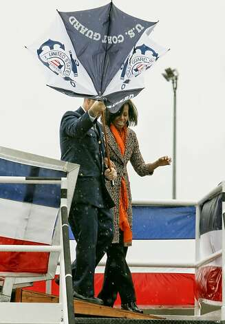 The wind and rain whip through the area as First Lady Michelle Obama is escorted to the stage by Command Senior Chief David Stephens, as she was on hand to help commission the United States Coast Guard Cutter Stratton on Coast Guard Island, on Saturday March 31, 2012, in  Alameda, Ca. Photo: Michael Macor, The Chronicle