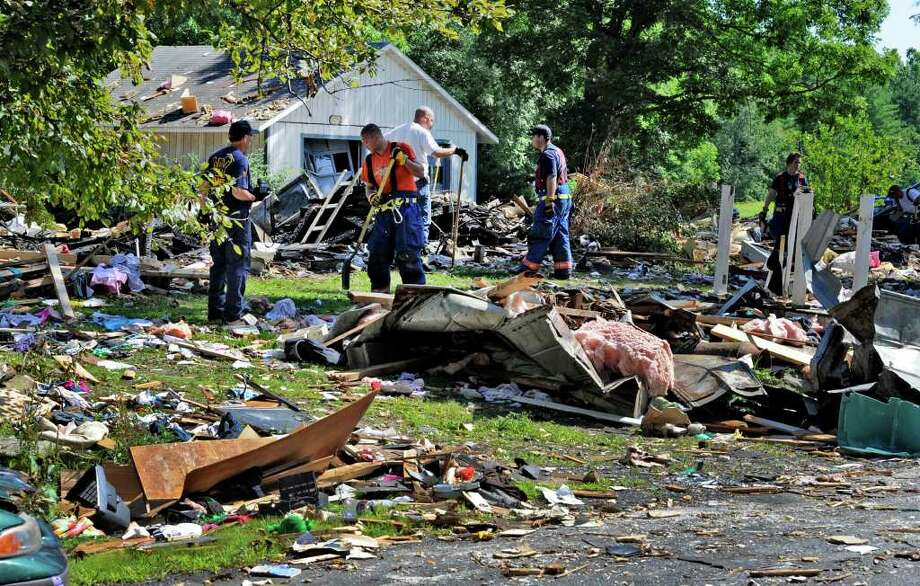 Investigators and firefighters comb the explosion site Thursday morning July 14, 2011 on Route 29 in Salem, N.Y., for clues. (Skip Dickstein / Times Union archive) Photo: SKIP DICKSTEIN / 2011