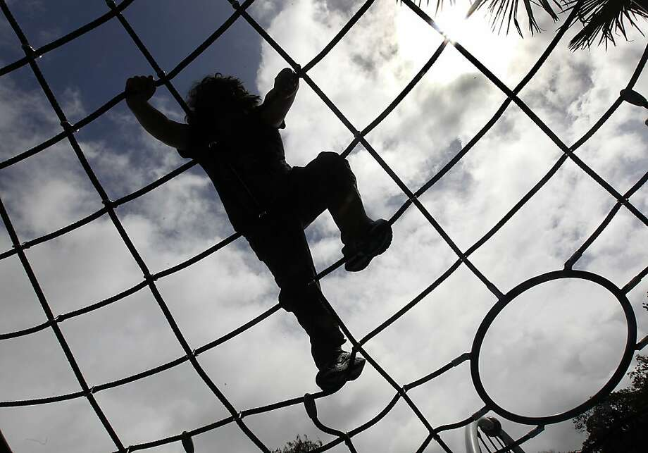 A boy climbs up a rope lattice at the Helen Diller Playground, which officially opened to the public at Dolores Park in San Francisco, Calif. on Saturday, March 31, 2012. Photo: Paul Chinn, The Chronicle