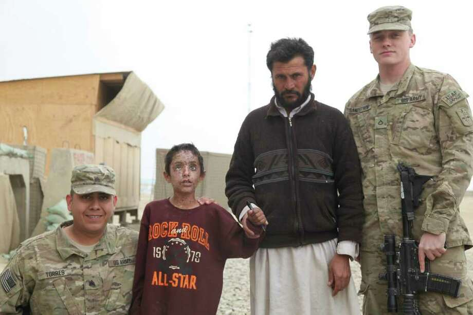 An undated handout photo of, from left, Sgt. Michael Torres, 8-year-old Mateen and his neighbor Sultan, and Pvt. Cody Sandstrom at Combat Outpost Kushamond in Paktika Province. Mateen was blinded by a blast and rescued. In addition to the bureaucratic hesitation, after years of emphasizing better community relations, most soldiers are routinely involved in providing services to Afghans and think of their actions as just part of their jobs. (Courtesy of the United States Army via The New York Times) -- EDITORIAL USE ONLY Photo: THE UNITED STATES ARMY / THE UNITED STATES ARMY