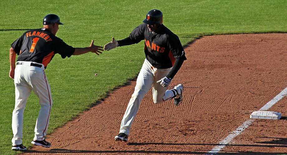 San Francisco Giants 3rd base coach Tim Flannery extends his hand to Joaquin Arias after his two-run homer in the seventh of of their spring training baseball game with the Cincinnati Reds Saturday, March 31, 2012 in Scottsdale, Ariz. Cincinnati won 10-2. Photo: Lance Iversen, The Chronicle