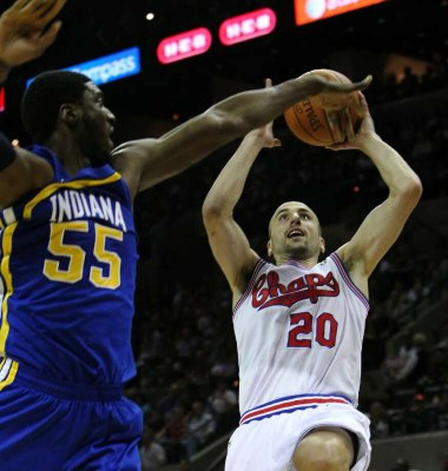 Spurs' Manu Ginobili (20) attempts a fade away shot against the Indiana Pacers' Roy Hibbert (55) in the first half at the AT&T Center on Saturday, Mar. 31, 2012. Kin Man Hui/Express-News. (San Antonio Express-News)