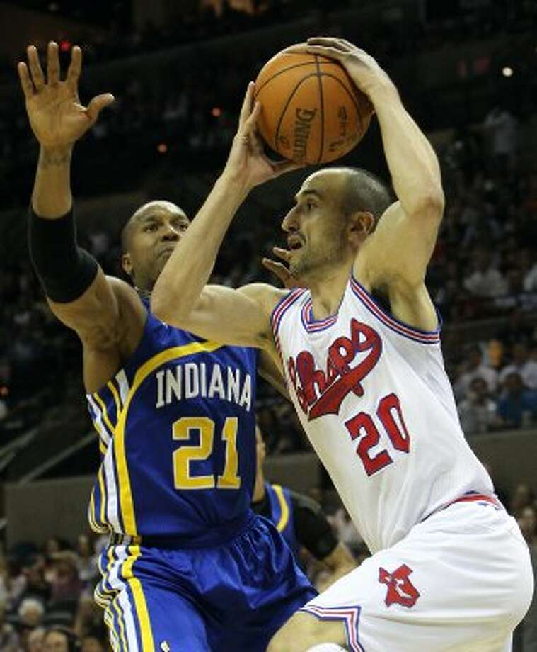Spurs' Manu Ginobili (20) drives around the basket looking to make a pass against the Indiana Pacers' David West (21) in the first half at the AT&T Center on Saturday, Mar. 31, 2012. Kin Man Hui/Express-News. (San Antonio Express-News)