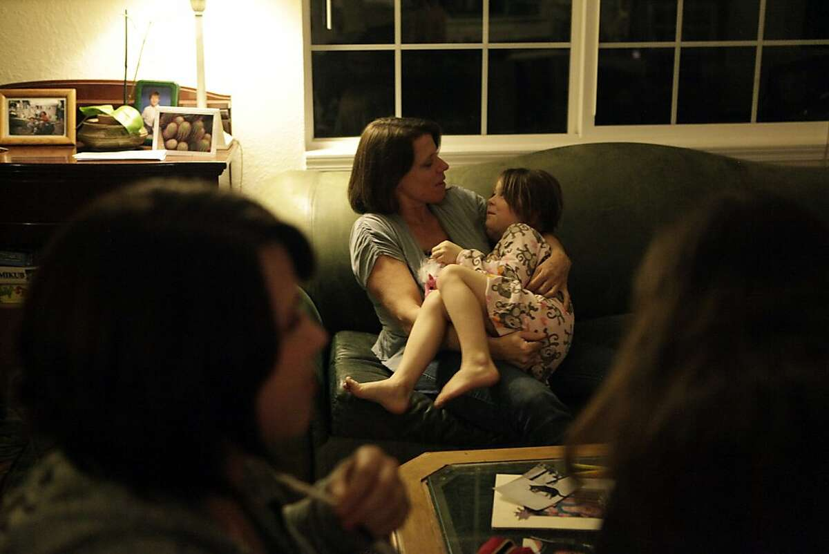 Lori MacKenzie (right) of Napa holds her daughter Caroline MacKenzie Bull, 6, as they talk on the couch in the living room of their home the day before her DIEP Flap Breast Reconstruction procedure on Tuesday, February 21, 2012 in Napa, Calif. MacKenzie was told she would be restricted to lifting 10 lbs after her surgery.