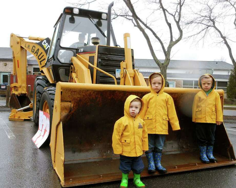 Andrew, Matthew and Joseph Martino, of Westport, stand in the bucket of a front loader at the Touch-A-Truck event Saturday at Coleytown Elementary School. Photo: Mike Lauterborn / Westport News contributed