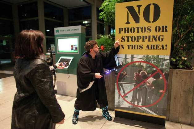Chris Templeton strikes a pose next to a sign advising that photography is not allowed during Emerald City Comicon on Saturday, March 31, 2012. The annual comic book and pop culture convention is the largest such convention in the Pacific Northwest. Photo: JOSHUA TRUJILLO / SEATTLEPI.COM