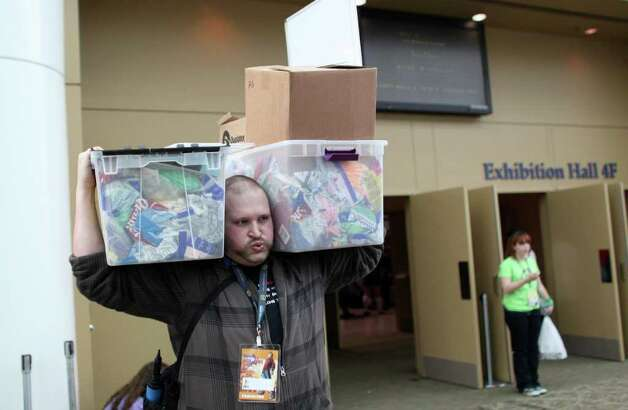 Brandon Owens hoists some of his collection during Emerald City Comicon on Friday, March 30, 2012. The annual comic book and pop culture convention is the largest such convention in the Pacific Northwest. Photo: JOSHUA TRUJILLO / SEATTLEPI.COM
