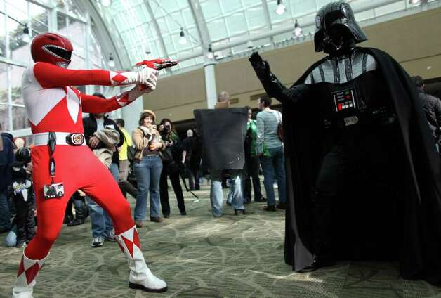 Power Ranger Cory Aurandt takes a shot at Darth Vader during Emerald City Comicon on Friday, March 30, 2012. The annual comic book and pop culture convention is the largest such convention in the Pacific Northwest. Photo: JOSHUA TRUJILLO / SEATTLEPI.COM
