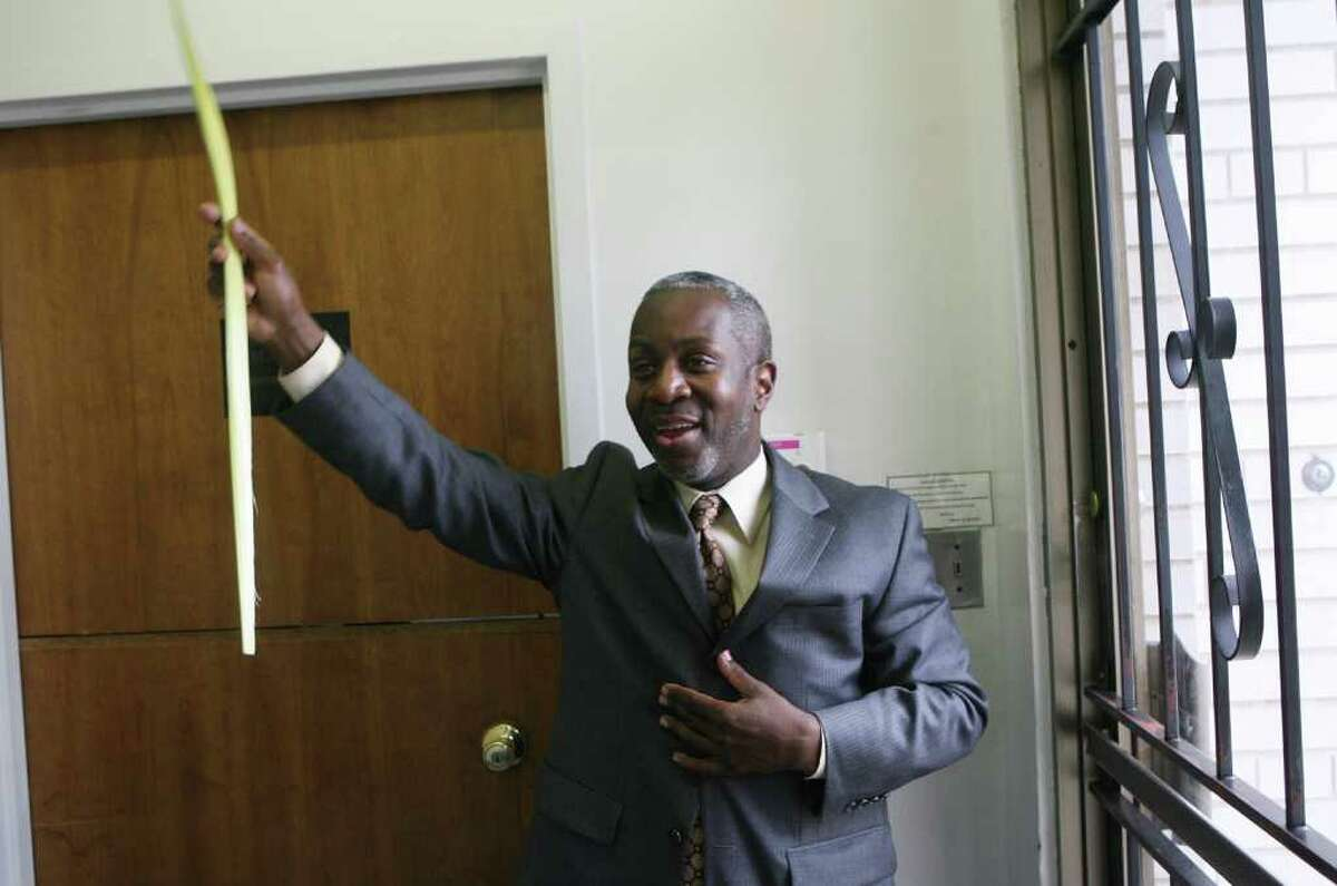 Anthony McCrae holds up palm leaves at Triumphant Ministries In Bridgeport, Conn. on Sunday, April 1, 2012.