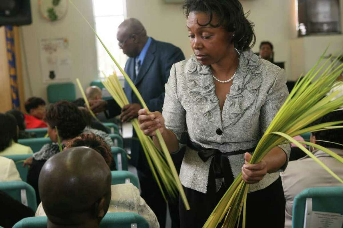 Carla Wright hands out palm leaves at Triumphant Ministries In Bridgeport, Conn. on Sunday, April 1, 2012.