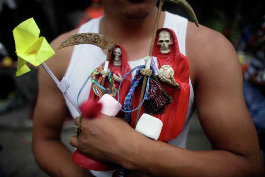 A man carries two statues of the folk saint Santa Muerte, or Death Saint in Mexico City.  Mexican prosecutors are investigating a family outside a small town near the U.S. border as alleged members of a cult who sacrificed three people to the Saint Death. Photo: Associated Press