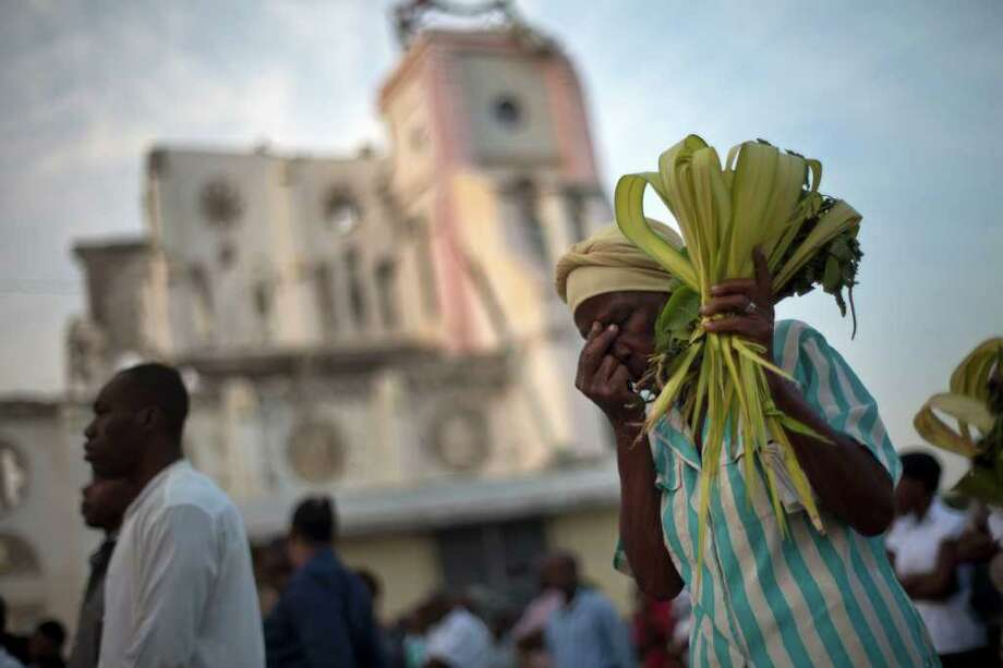 A woman prays as she holds palm fronds during an outdoor Palm Sunday Mass in front of the earthquake damaged cathedral in Port-au-Prince, Haiti. Photo: Associated Press