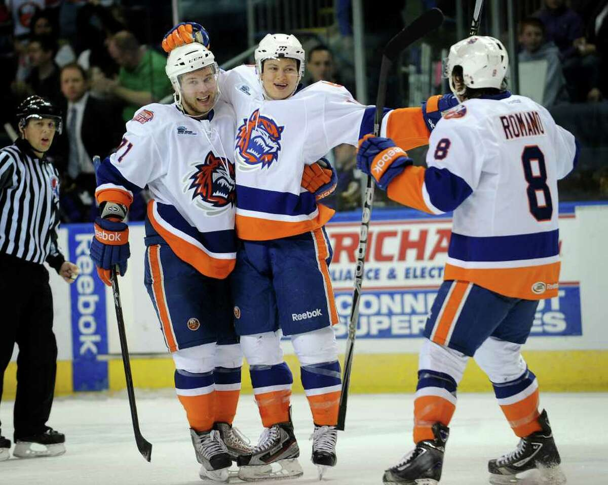 From left; Sound Tigers Mark Katic, Rhett Rakhshani, and Tony Romano celebrate Rakhshani's overtime goal which gave the team a 3-2 victory over Manchester at the Webster Bank Arena in Bridgeport on Sunday, April 1, 2012.