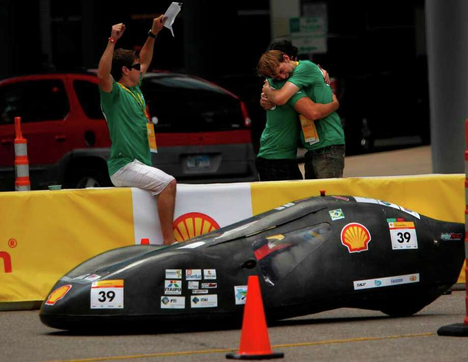Felipe Arce Boiarski throws hands in the air as Vitor Trentini Neto embraces Andre William Tonatto, of Brazil's Unioeste-Universidade Estadual Do Oeste Do Parana, as their driver arrives to the pit upon completing laps during the Shell Eco-Marathon Americas 2012 on Sunday, April 1, 2012, in Houston. High school, university, and college students test vehicles they have designed and built to see which can go the farthest distance using the least amount of fuel. Photo: Mayra Beltran, Houston Chronicle / © 2012 Houston Chronicle