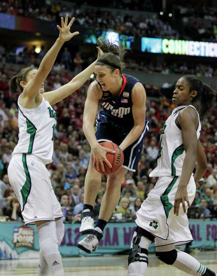 Connecticut guard Kelly Faris (34) passes between Notre Dame forward Natalie Achonwa (11) and Notre Dame forward Devereaux Peters (14) during overtime in the NCAA women's Final Four semifinal college basketball game, in Denver, Sunday, April 1, 2012. Notre Dame won 83-75. (AP Photo/Julie Jacobson) Photo: Julie Jacobson, Associated Press / AP