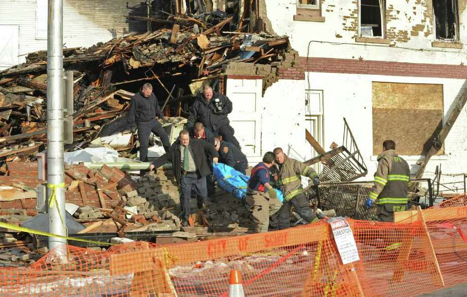 Police and firefighters remove a body that was found in the rubble during a demolition of a house on McClellan Street in Schenectady, NY. The house had burned downed three weeks ago after a fire. (Lori Van Buren / Times Union) Photo: Lori Van Buren / 00011611A