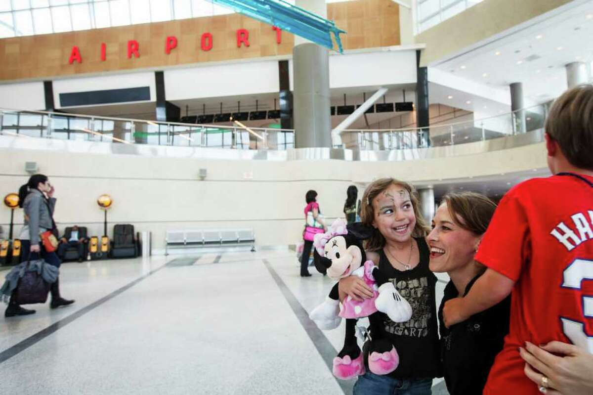 """Carmen Watson) hugs her daughter Jessie, 5, and son Cohen, 7, on their arrival at Hobby with their grandmother from a week-long trip to Walt Disney World. """"Hobby Airport is the only place we ever fly out of,"""" Watson said."""
