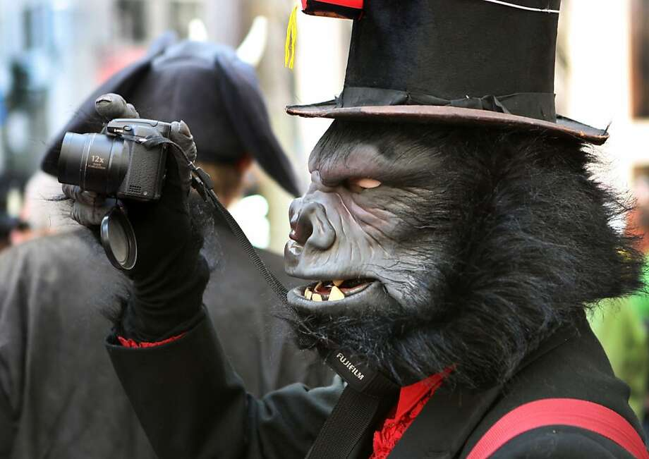 Kaosmic Kat, dressed as a gorilla, takes a snapshot with her camera during the annual St. Stupid's Day parade in San Francisco. People dressed in outlandish costumes marched along Montgomery and Columbus in San Francisco on Sunday afternoon for the 34th annual St. Stupid's Day Parade. The event was sponsored by the First Church of the Last Laugh. Photo: Kevin Johnson, The Chronicle